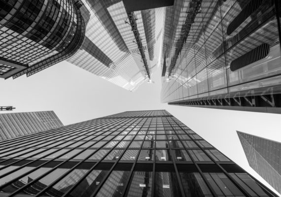 Highly detailed abstract wide angle view up towards the sky in the financial district of London City and its ultra modern contemporary architecture. Shot on Canon EOS R full frame system with 14mm wide prime lens. Monochrome edit in Black and White image with high contrast.